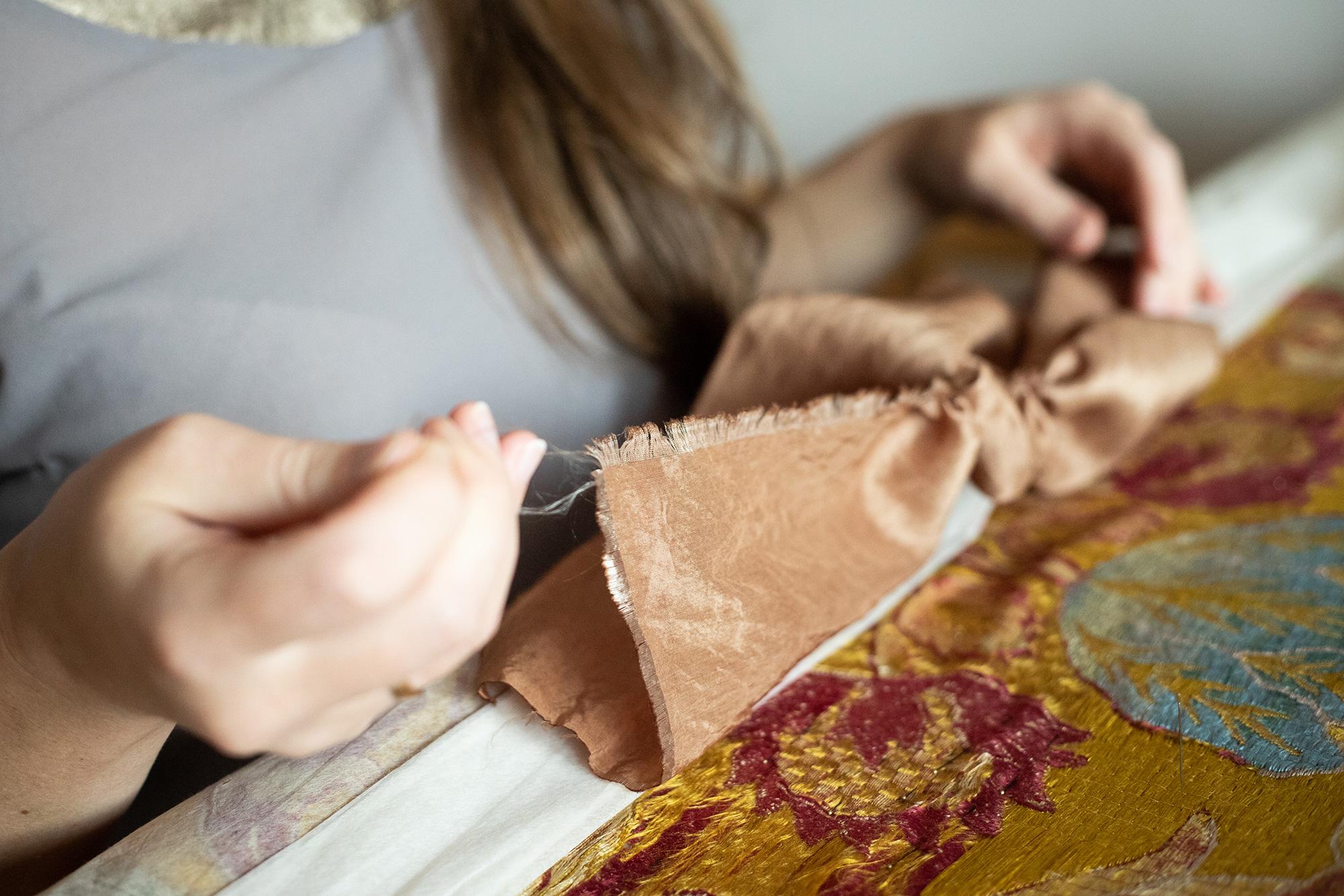 Magdalena wypruwa pojedynczą nitkę z tkaniny jedwabnej.
