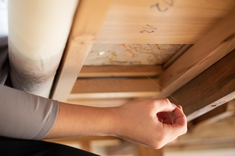 Przewlekanie nici, które zabezpieczają obiekt. Prawa ręka konserwatora pracuje od dołu, lewa ręka od góry.