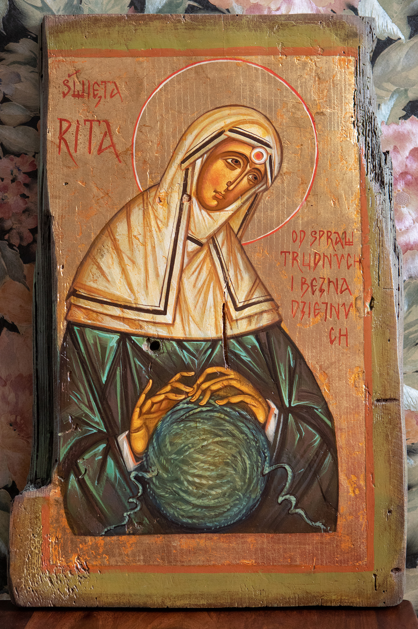 """Św. Rita z atrybutem ciernia (z korony cierniowej Zbawiciela) wbitym głęboko w jej czoło. Święta rozsupłuje """"węzeł gordyjski"""" w kształcie kuli."""